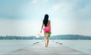 Fit woman with long dark hair in hot pink bikini walking away on a pier.