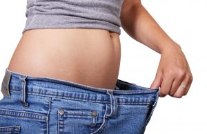 woman pull out waistband to show jeans are too big for waist