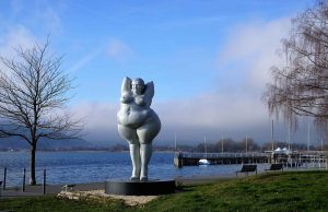 sculpture of nude obese woman in park