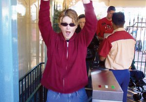Woman with sunglasses and red hoodie walking through turnstile wth arms overhead
