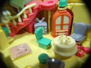 Toy furniture inside of a brightly colored dollhouse